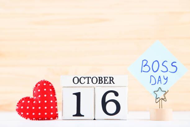 día del jefe de la inscripción, calendario de madera y corazón de tela sobre fondo de madera - boss's day fotografías e imágenes de stock