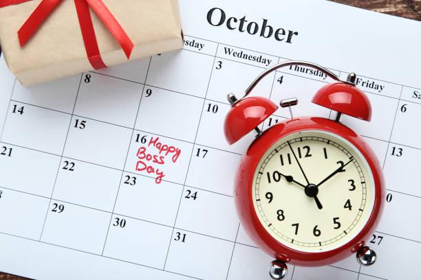 feliz día del jefe inscripción en calendario con reloj alarma y caja de regalo - boss's day fotografías e imágenes de stock