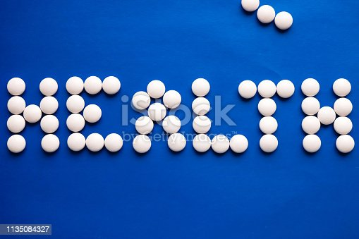 91708255 istock photo Inscription Health made of white pills on blue table. Medicine concept. 1135084327