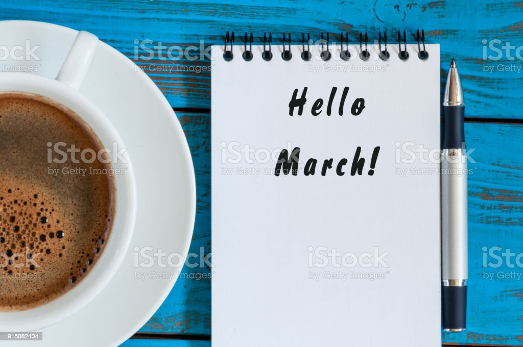 Inscription HELLO MARCH in notepad near morning coffee cup. Top view. Beginning of spring concept stock photo
