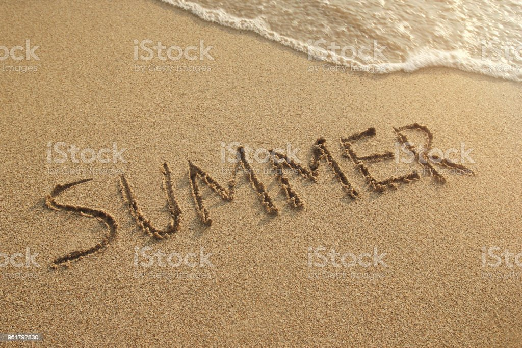 Inscription on a wet sand (Summer) with sea waves on a sunset, top view. royalty-free stock photo