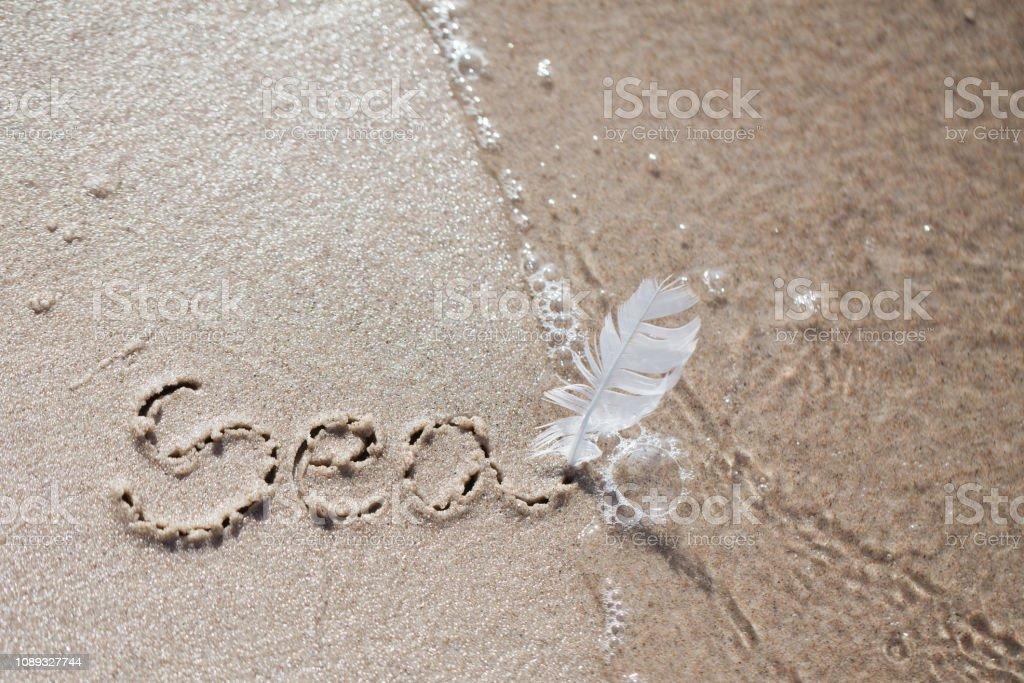 inscription on the beach 'sea'. holiday, beach, inscription on the sand, stock photo