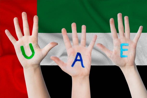 uae inscription on the children's hands against the background of a waving flag of the united arab emirates - uae national day стоковые фото и изображения