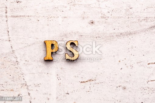 istock Inscription PS post scriptum abbreviation in wooden letters on a light background 1134970311