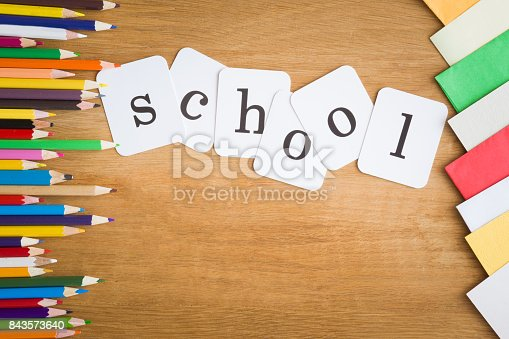 istock Inscription school with color pencils on the wooden table. Education concept. Top view. 843573640