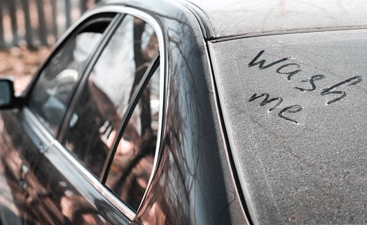 Inscription wash me on the dirty car window