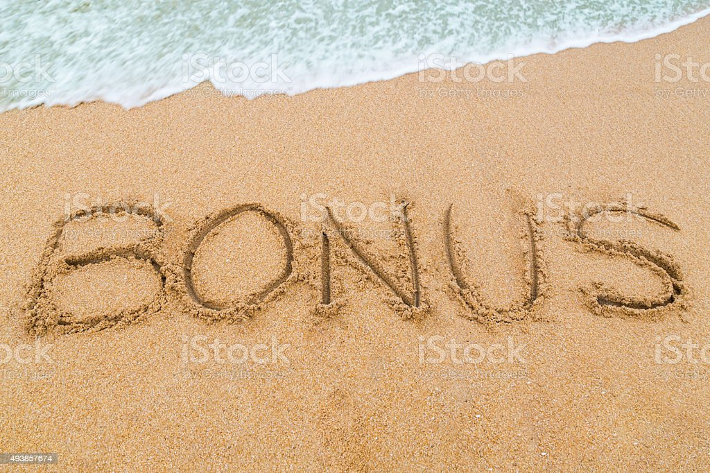 BONUS inscription written on sandy beach with wave approaching stock photo