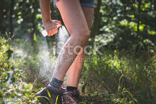 Woman applying mosquito repellent on her legs in forest.