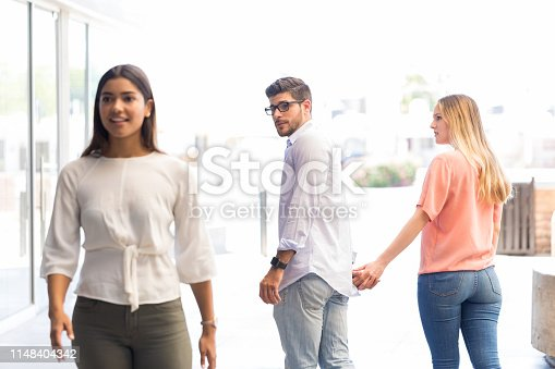 Young man checking out other woman while walking with girlfriend in shopping center