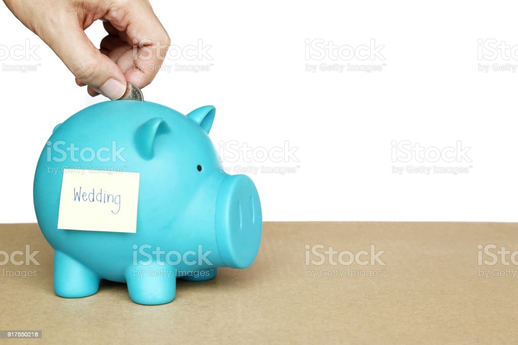 insert coins in blue piggy bank with sticky note and wedding word on concept of saving money for wedding stock photo