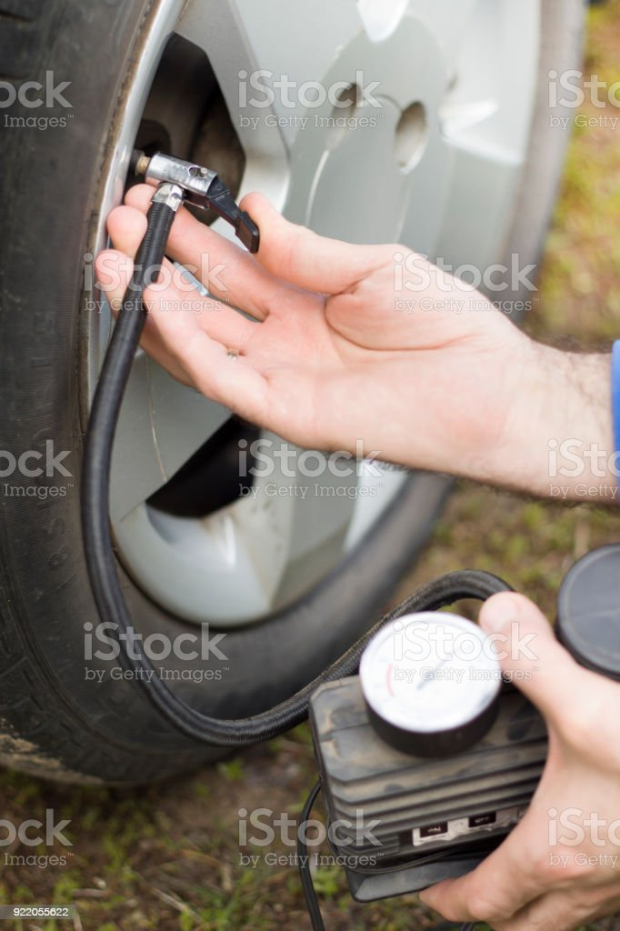 Insert the tip into the valve and pump the car wheel with a portable compressor at 12V stock photo