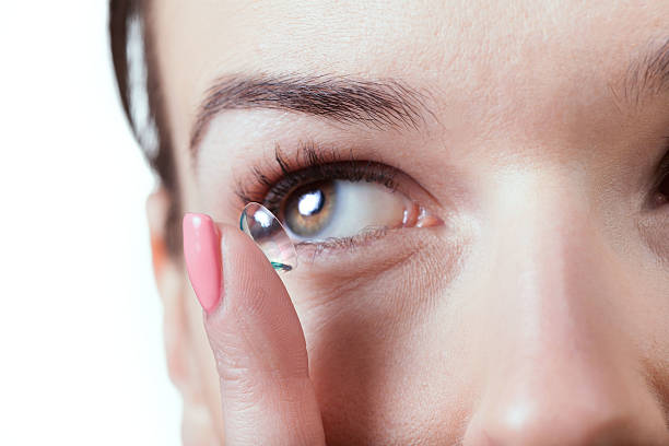 Inserting a contact lens in female eye stock photo