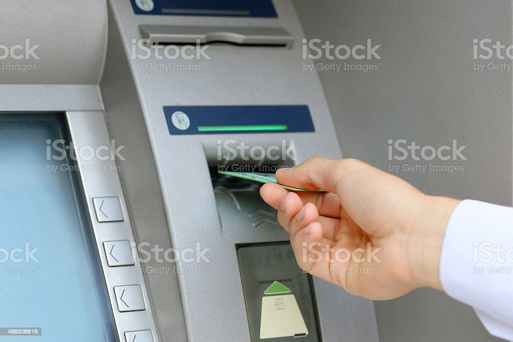 inserting a credit card to ATM stock photo