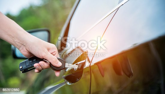 Woman hand inserting key in car door.