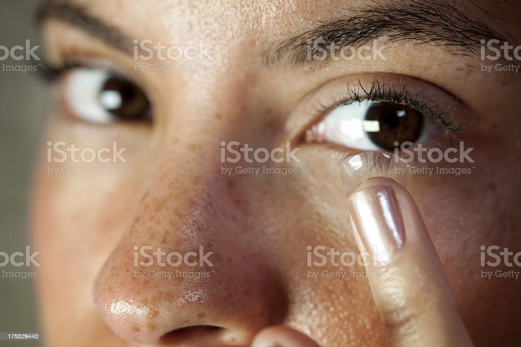 Inserting contact lens stock photo
