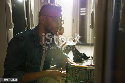 istock Inserting motherboard into supercomputer server rack 1153742626