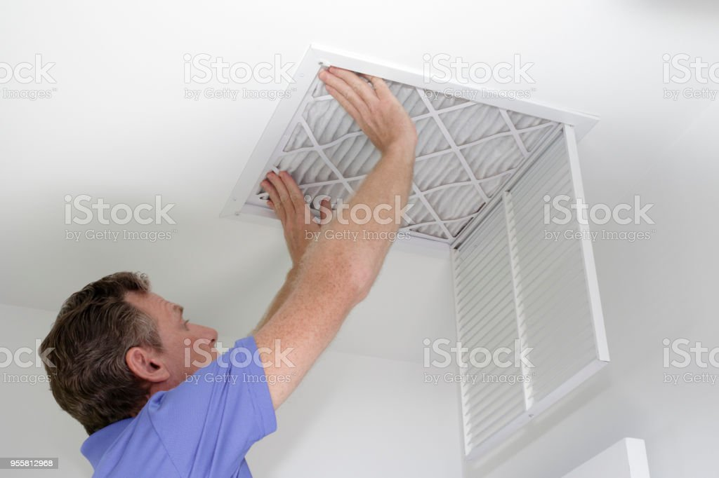 Inserting New Air Filter in Ceiling stock photo