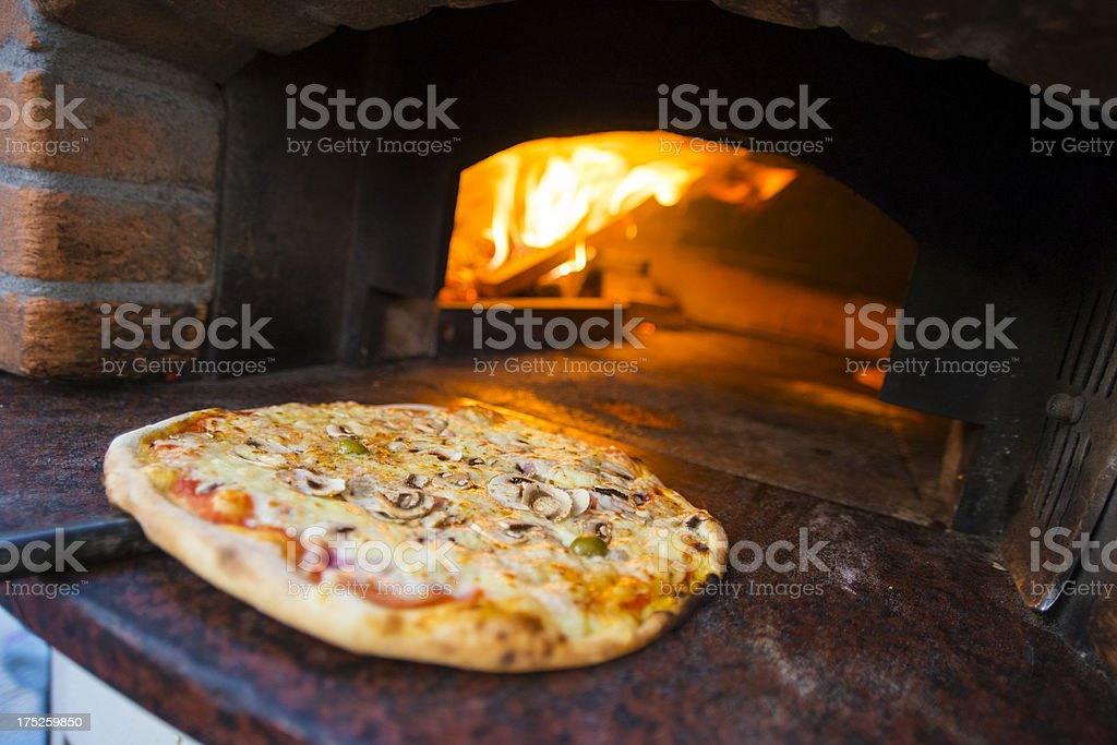 Inserting pizza in oven stock photo