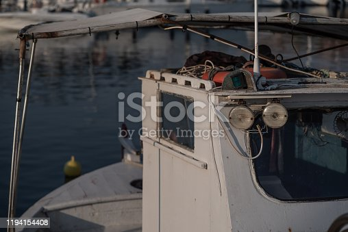 Inshore fishing boat and tackle moored in a harbour at dusk.  Sithonia, Greece.