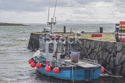 Inshore fishing boat moored at a stone pier at Kircubbin, County Down (Northern Ireland).  In the distance is Strangford Lough and the outline of the Mourne Mountains.