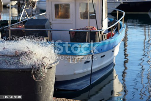 Inshore fishing boat with net and tackle in cool light