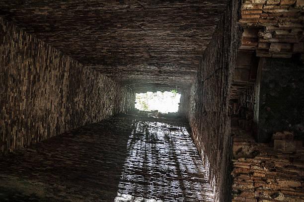 innentasche mit gemauertem kamin mit licht am ende - tunnelkamin stock-fotos und bilder