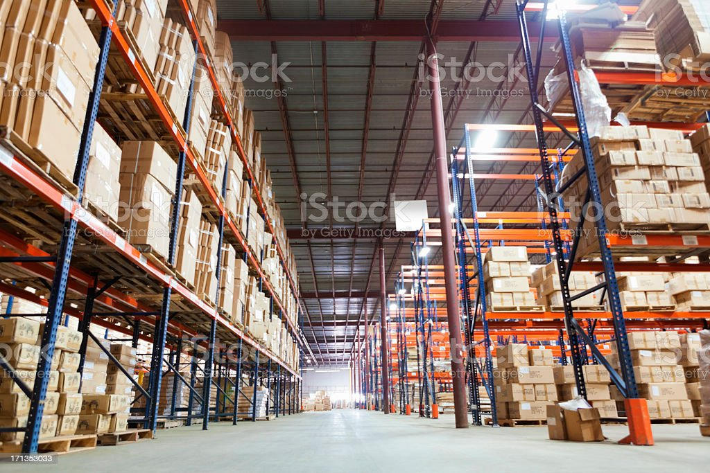 Inside a shipping distribution warehouse lined with shelves of boxes royalty-free stock photo