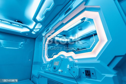 Inside a small cozy room in a capsule hotel - a futuristic interior with a light control panel, electric charging and an alarm clock filled with calm blue light