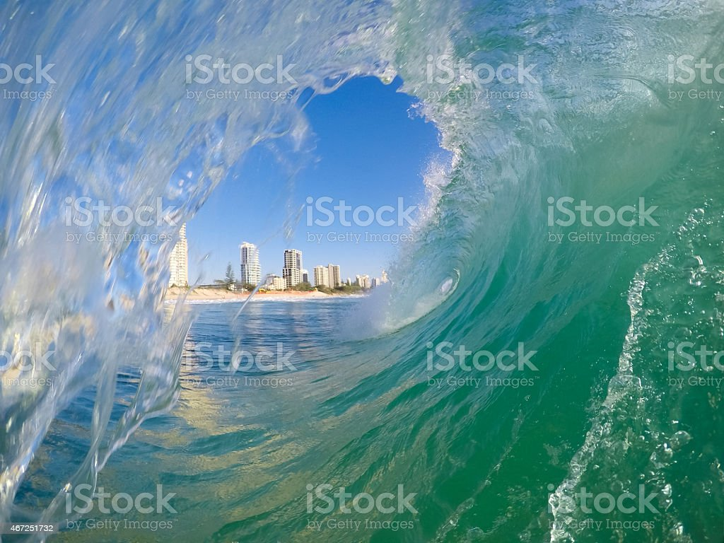 Inside a wave breaking on the beach with blue sky stock photo