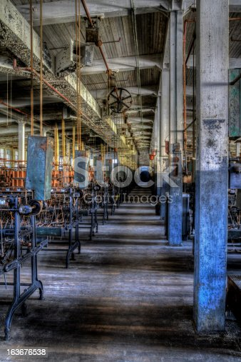 The dark and gloomy interior of a long abondened mill with machinery still in place.  High Dynamic Range photo.