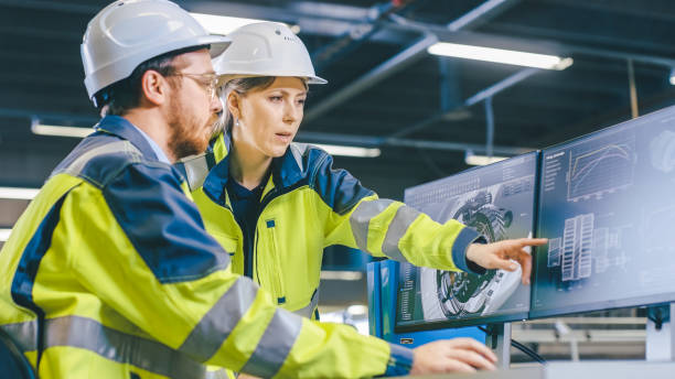 dentro del ingeniero mecánico masculino de fábrica y el ingeniero jefe femenino trabajan juntos en el ordenador personal, discuten los detalles del diseño del modelo del motor 3d. - ingeniero fotografías e imágenes de stock