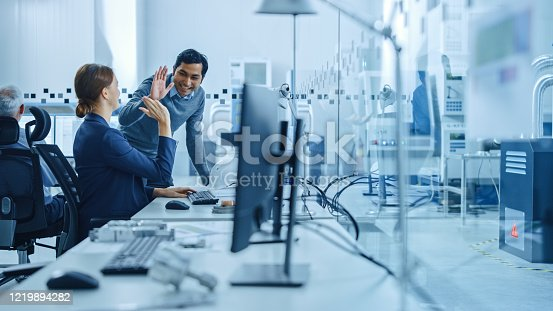 921019684 istock photo Inside Factory Office: Male Project Supervisor Talks to a Female Industrial Engineer who Works on Computer, Give High Five. In Workshop: Workers Use High-Tech Industry 4 CNC Machinery, Robot Arm. 1219894282