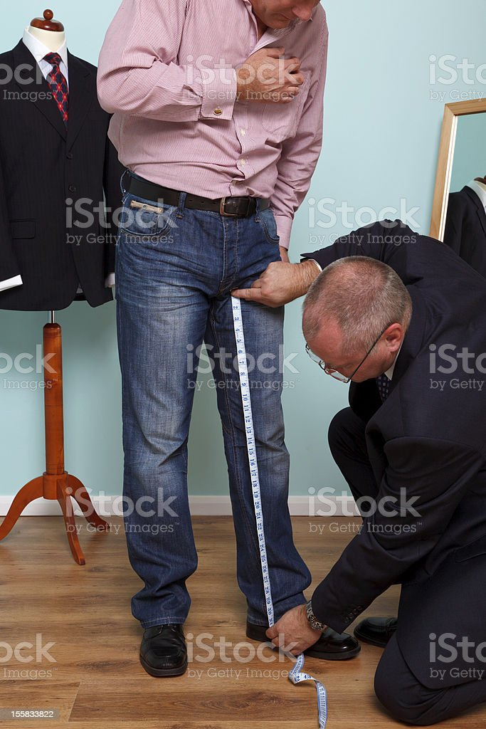 Inside leg being measured by a tailor during suit fitting stock photo