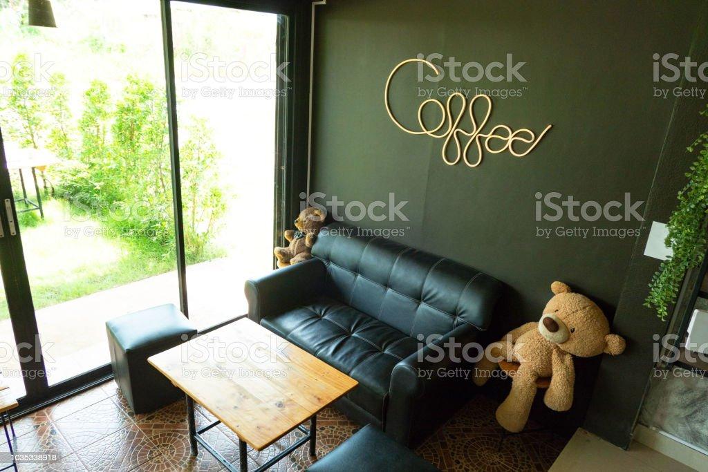 Im Modernen Café Dekorativen Schwarzen Sofa Und Holztischen ...