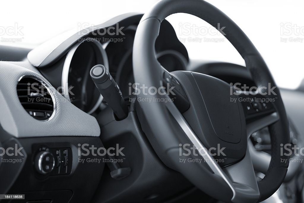 inside of a car showing a black car steering wheel royalty-free stock photo