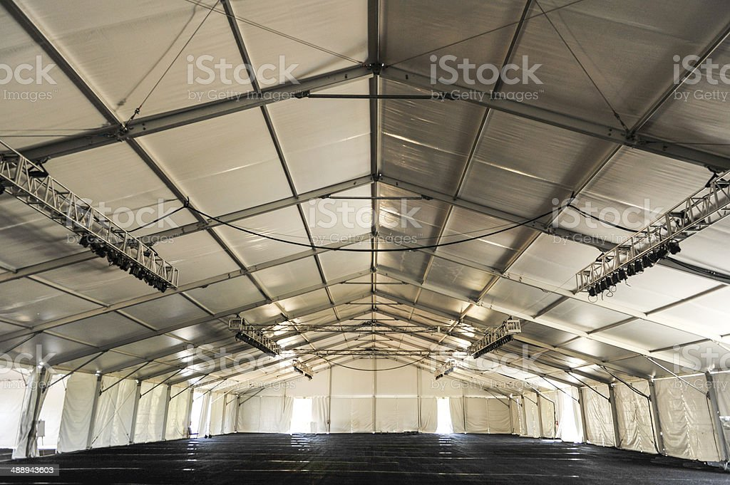 Inside of a huge white tent with rafters stock photo