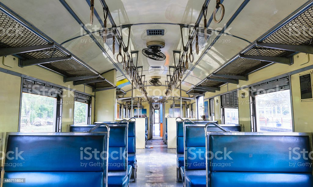 Inside of an old train. Blue vintage seats. Natural light from window.
