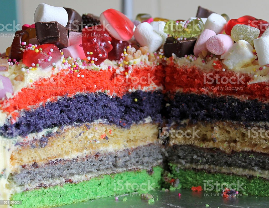 Inside of multi-coloured rainbow cake with sweets on top stock photo