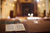 istock Inside of Orthodox Synagogue with open book in the Hebrew language in the foreground. selective focus 1047603902