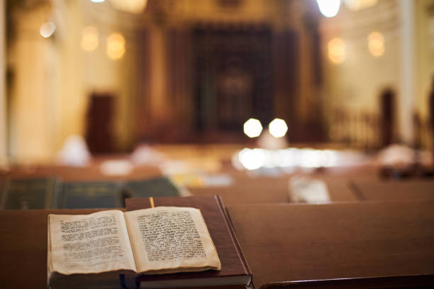 wewnątrz prawosławnej synagogi z otwartą księgą w języku hebrajskim na pierwszym planie. selektywne skupienie - judaizm zdjęcia i obrazy z banku zdjęć
