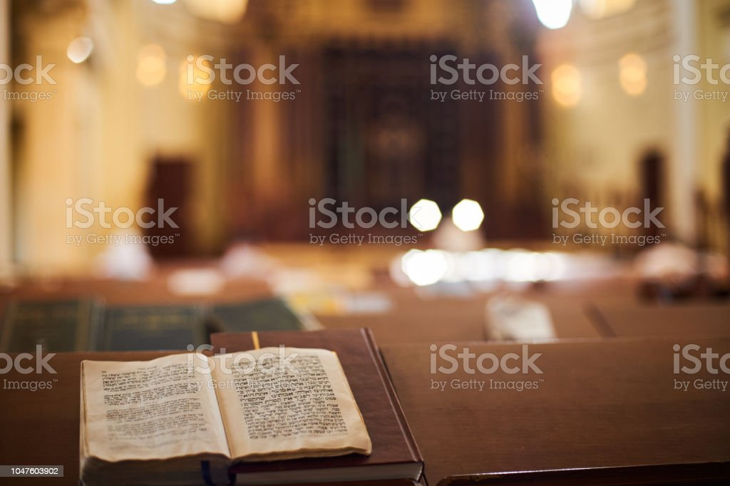 Inside of Orthodox Synagogue with open book in the Hebrew language in the foreground. selective focus stock photo