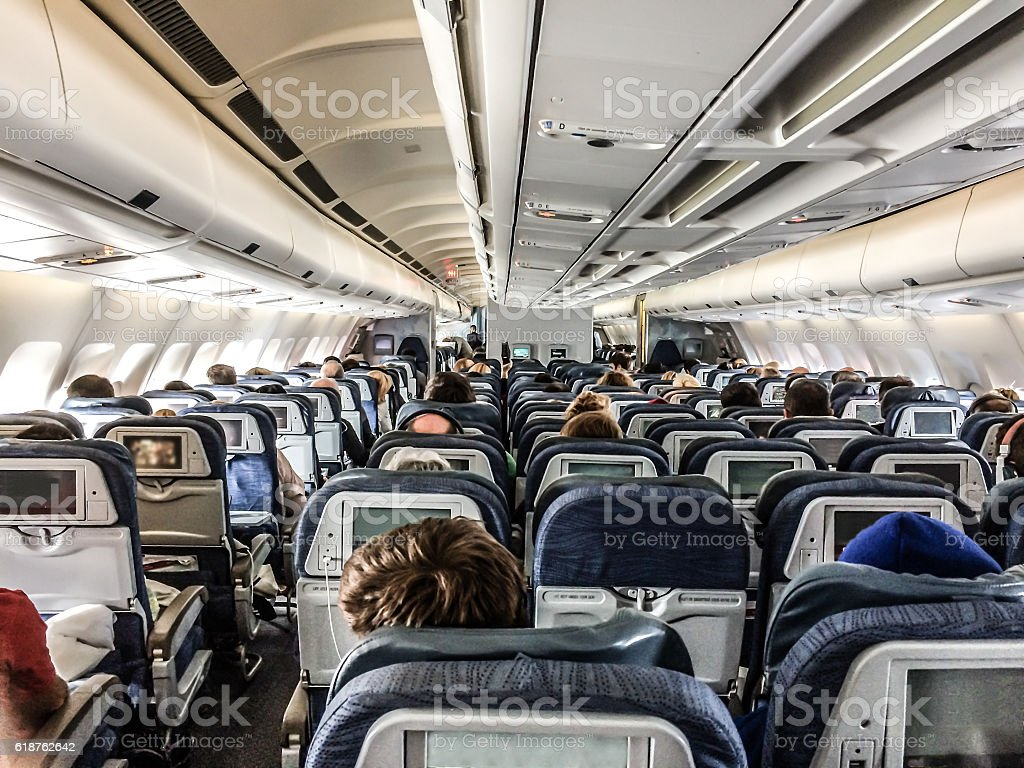 Inside of plane seen from rear with passengers stock photo