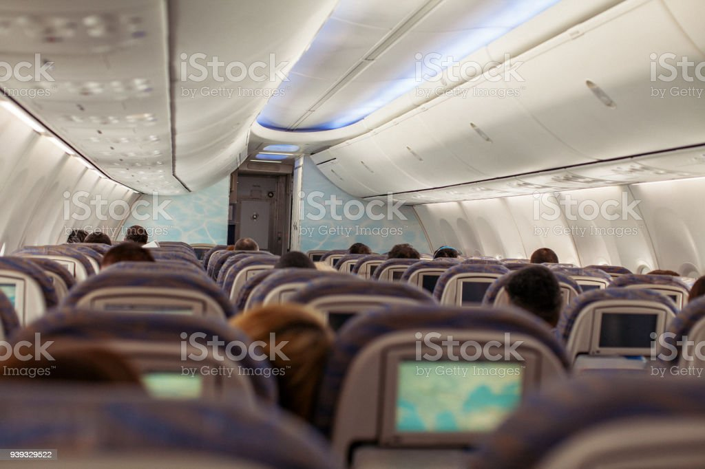 Inside of airplane during commercial flight. People sitting in their...