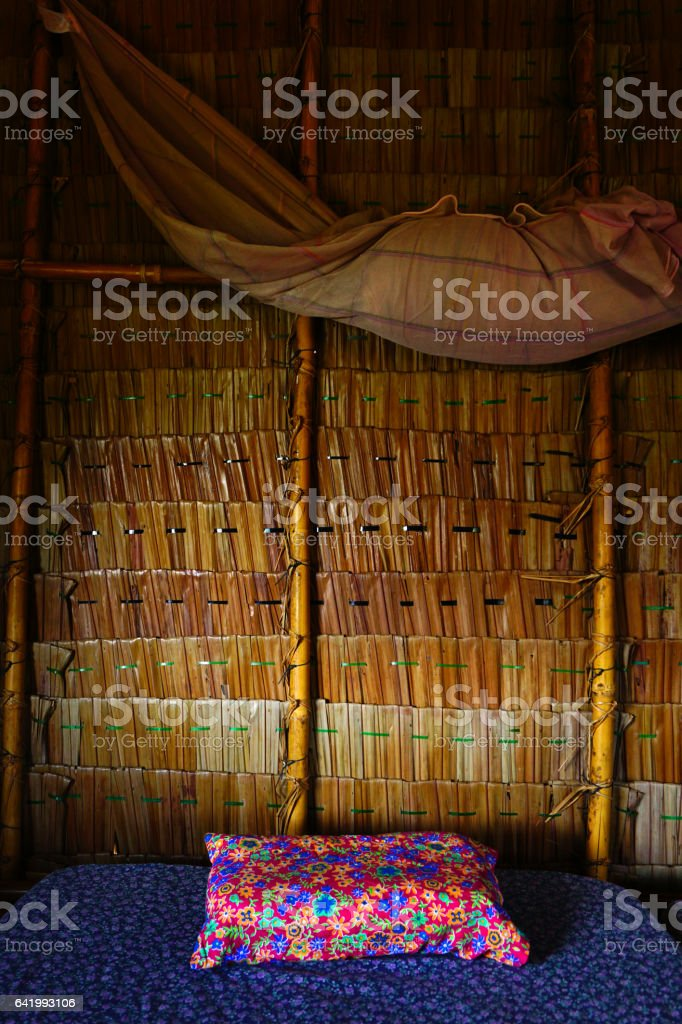 inside of the staw house with bed and pillow. stock photo