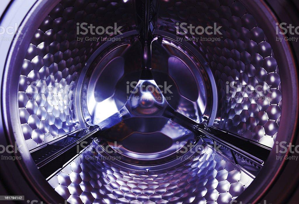 Stainless steel drum of household washing machine reflecting light.