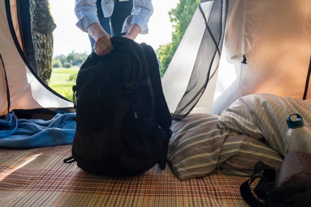in-out camping zelt blick, hände greifen den rucksack - zelt stehhöhe stock-fotos und bilder