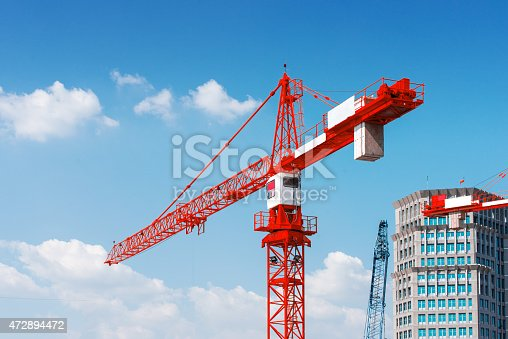 Inside place for tall buildings under construction and cranes under a blue sky