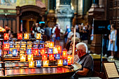 This image shows tourists sat on pews in the foreground beside votive candles in the Cathedral of Notre Dame de Fourviere, Lyon, France. The cathedral was completed in 1884.
