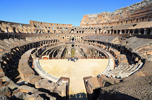 Inside the Colosseum, Rome. Super Wide Angle Super wide angle view of the Colosseum, inside the  Colosseum and incidental people visiting it.  rome, Italy.  High contrast shot in morning sun. palatine hill rome stock pictures, royalty-free photos & images