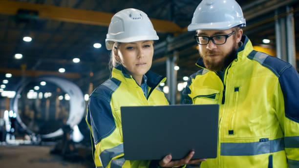 in den schweren industriebetrieb weibliche wirtschaftsingenieur hat laptop und diskussion mit dem projekt-manager. sie tragen hart hüte und sicherheitswesten. in den hintergrund-schweißen / metallbearbeitung im gange. - projektmanager stock-fotos und bilder